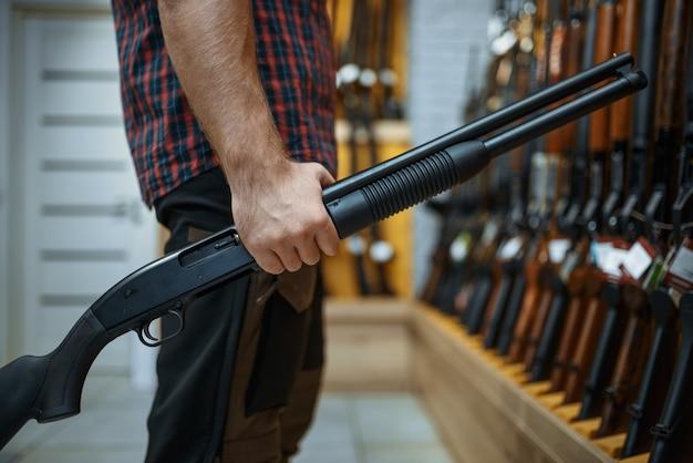 Mężczyzna z karabinem w gablocie w sklepie z bronią