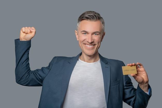 Mężczyzna z kartą kredytową podnoszący rękę zwycięsko