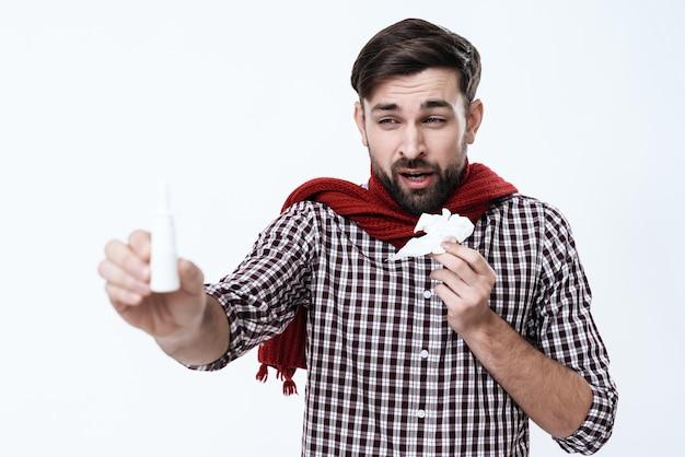 Mężczyzna z katarem kicha i pokazuje krople do nosa.