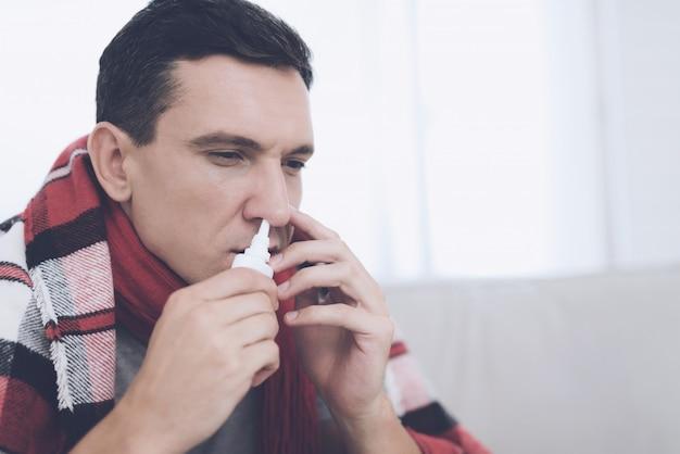 Mężczyzna z katarem zakopuje nos w domu.