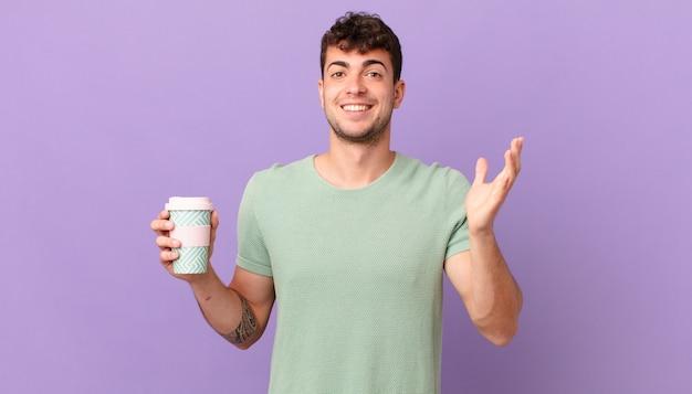 Mężczyzna z kawą czujący się szczęśliwy, zaskoczony i pogodny, uśmiechnięty z pozytywnym nastawieniem, realizujący rozwiązanie lub pomysł