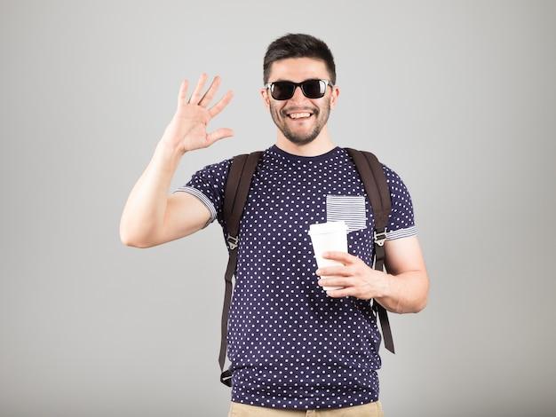 Mężczyzna z kawą i plecakiem na białym tle