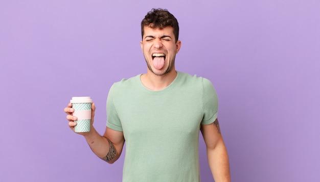 Mężczyzna z kawą o pogodnym, beztroskim, buntowniczym nastawieniu, żartujący i wystawiający język, dobrze się bawiący