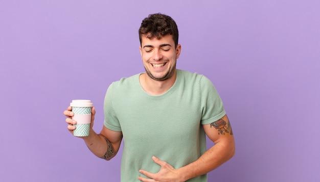 Mężczyzna z kawą śmiejący się głośno z jakiegoś śmiesznego żartu, szczęśliwy i wesoły, dobrze się bawiący
