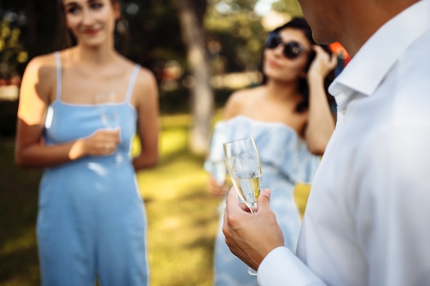 Mężczyzna z kieliszkiem szampana w dłoniach w towarzystwie świętujących ludzi. ślub, urodziny, rocznica.