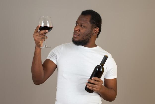 Mężczyzna z kieliszkiem wina w jednej ręce i butelką wina w drugiej, stojący przed szarą ścianą