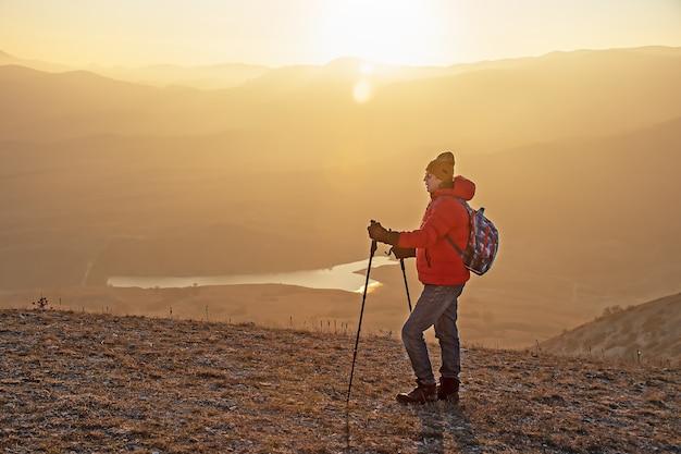 Mężczyzna z kijami do nordic walking stoi wysoko w górach i patrzy przed siebie.