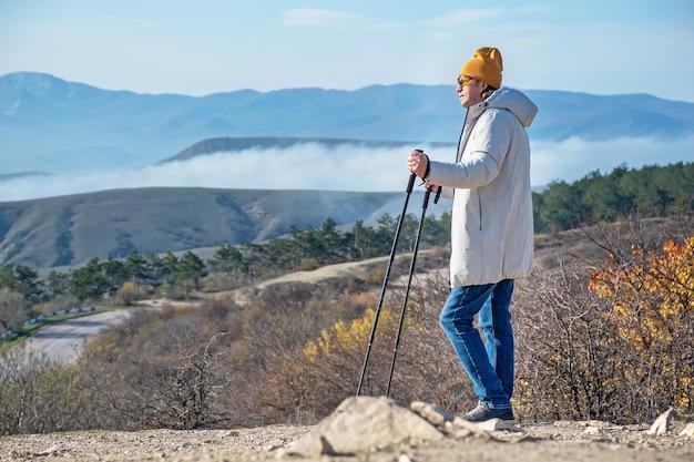 Mężczyzna z kijami do nordic walking stoi wysoko w górach i patrzy przed siebie