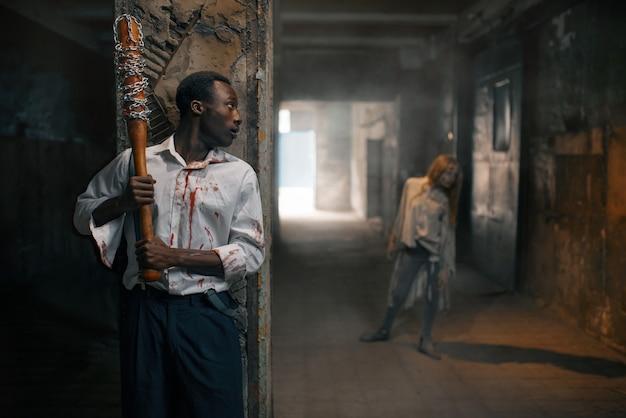 Mężczyzna z kijem baseballowym przygotowuje się do zabicia zombie, śmiertelny pościg w opuszczonej fabryce. horror w mieście, przerażający atak pełzających, apokalipsa zagłady, krwawy potwór
