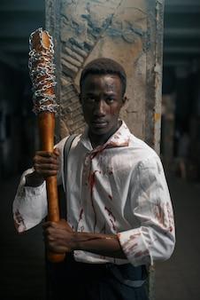 Mężczyzna z kijem baseballowym, śmiertelny pościg zombie w opuszczonej fabryce. horror w mieście, przerażający atak pełzających, apokalipsa zagłady, krwawy potwór
