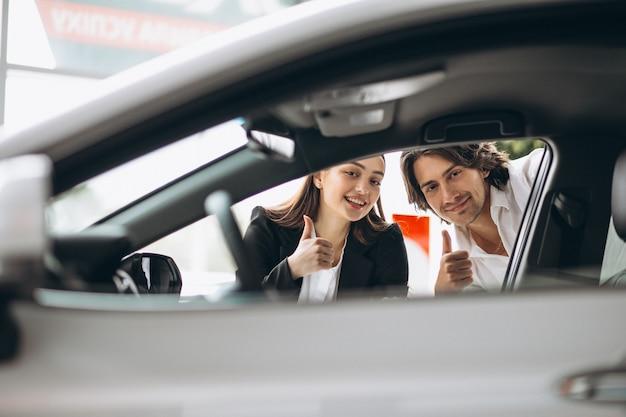 Mężczyzna z kobietą wybiera samochód w samochodowej sala wystawowej