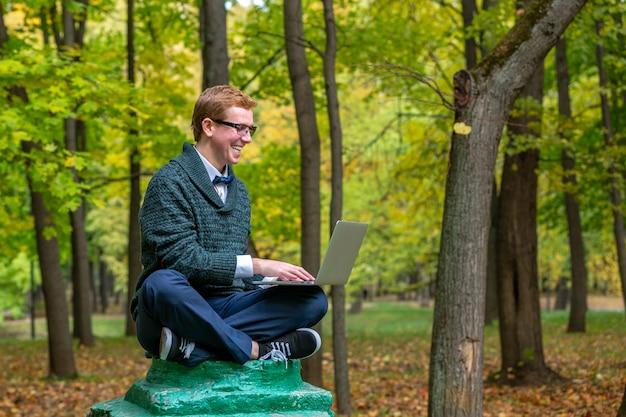 Mężczyzna z kolanami na piedestale, który udaje posąg w jesiennym parku