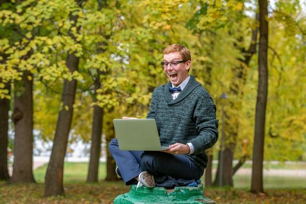 Mężczyzna z kolanami na piedestale, udający posąg w jesiennym parku. wpadnij na pomysł