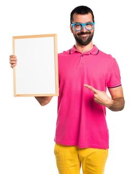 Mężczyzna z kolorowymi ubraniami trzyma pustego plakat