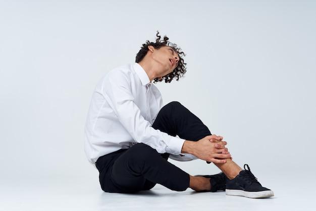Mężczyzna z kręconymi włosami w klasycznym garniturze i trampkach siedzi na podłodze i widok z boku copy space. wysokiej jakości zdjęcie