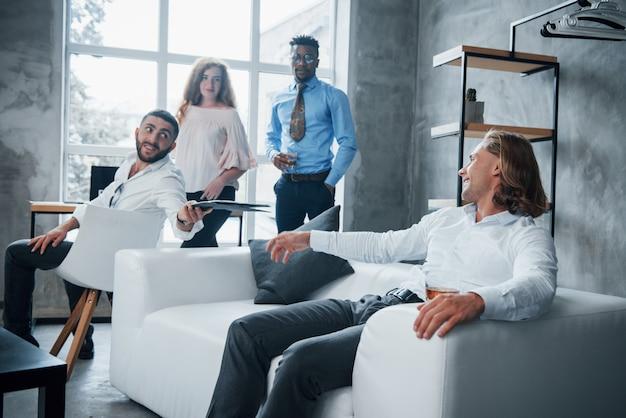 Mężczyzna z krótkimi włosami chce dzielić się swoimi wynikami z innym facetem. grupa wielorasowych pracowników biurowych w formalnych ubraniach rozmawiających o zadaniach i planach