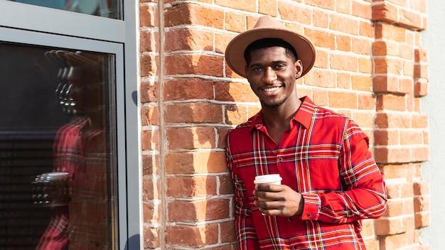 Mężczyzna z krótkimi włosami, trzymając kawę