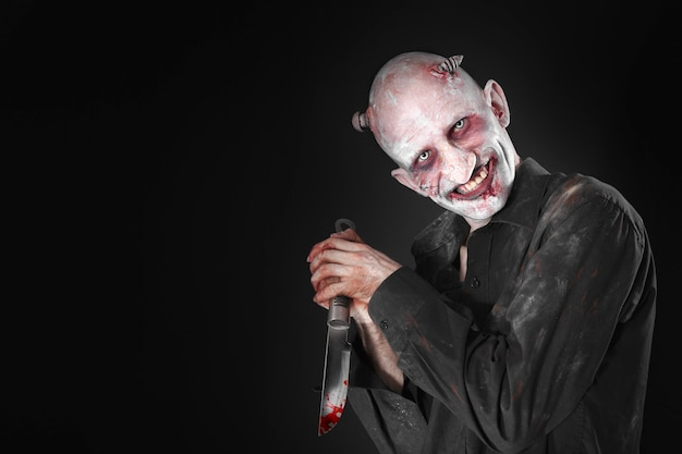 Mężczyzna z krwawym nożem przebrany za zombie na czarnym tle.