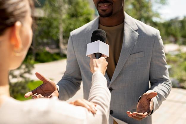 Mężczyzna, z którym dziennikarze przeprowadzają wywiady w plenerze
