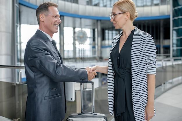 Mężczyzna z laptopem i kobieta w okularach, ściskając ręce