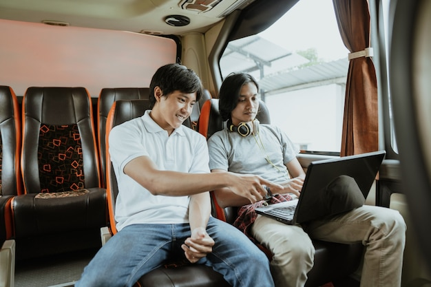 Mężczyzna z laptopem i słuchawkami rozmawia z przyjacielem o pracy, siedząc przy oknie w autobusie