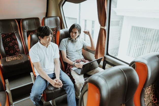 Mężczyzna z laptopem i słuchawkami rozmawia ze swoim przyjacielem, siedząc przy oknie w autobusie