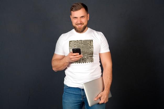 Mężczyzna z laptopem i telefonem, ono uśmiecha się, odizolowywający na szarej ścianie. biznesmen koncepcja, gadżety i nowe technologie, praca w internecie.