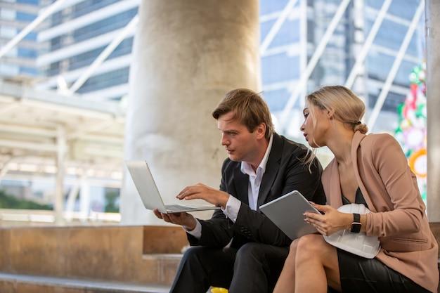 Mężczyzna z laptopem kobietą trzyma cyfrowej pastylkę podczas gdy siedzący na schody