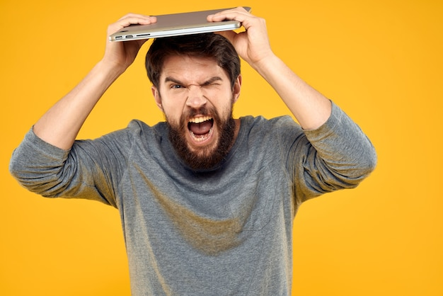 Mężczyzna z laptopem na czubku głowy na białym tle