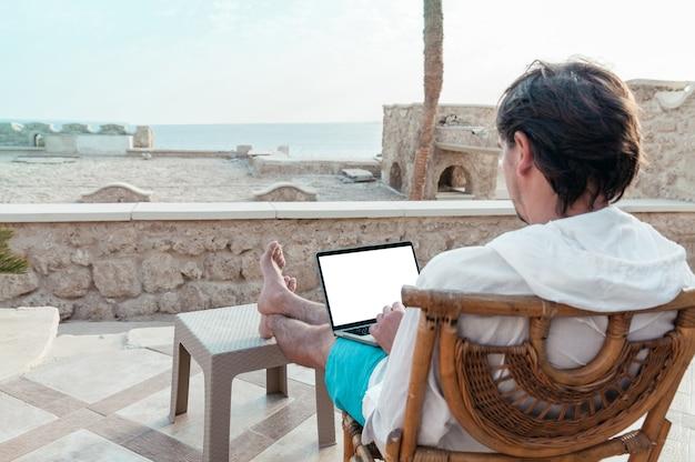 Mężczyzna z laptopem w rękach, odpoczywa i pracuje jako wolny strzelec na wakacjach