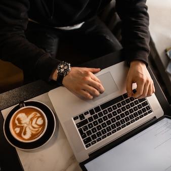 Mężczyzna z luksusowym zegarkiem w czarnej bluzie siedzi w kawiarni, pije kawę i pracuje na laptopie w pomieszczeniu