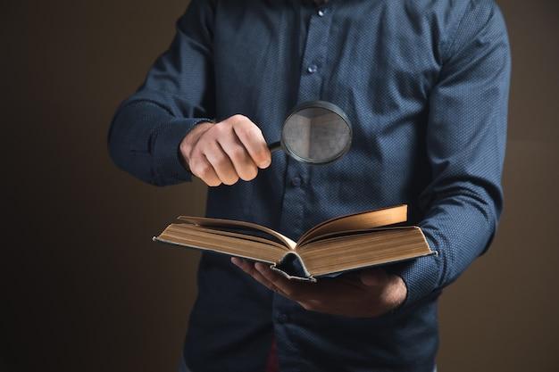 Mężczyzna z lupą czyta książkę na brązowej powierzchni