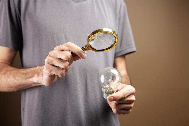 Mężczyzna z lupą patrzy na żarówkę. poszukiwanie pomysłu na pomysł. odkrywanie pomysłu