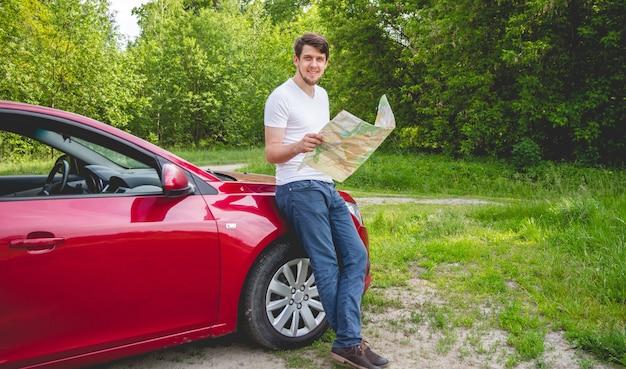 Mężczyzna z mapą w ręku stojący obok samochodu w lesie.