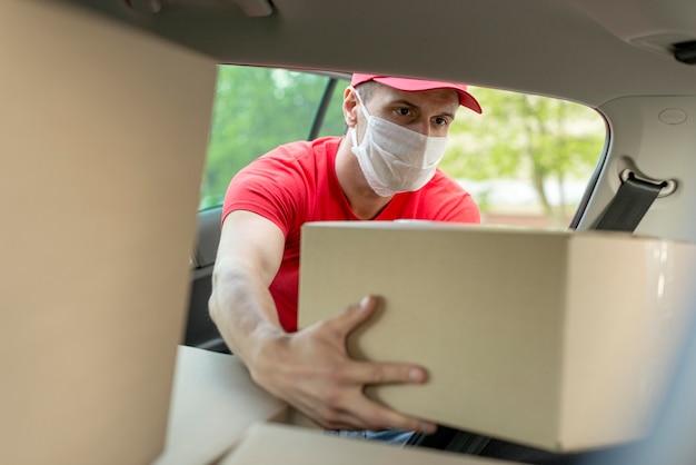 Mężczyzna z maską bierze pudełko