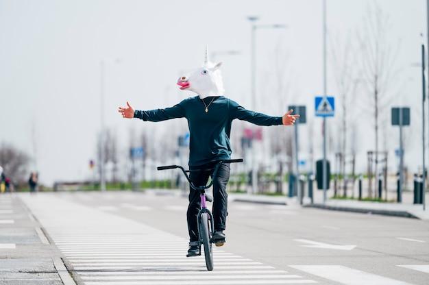 Mężczyzna z maską jednorożca, jazda na rowerze