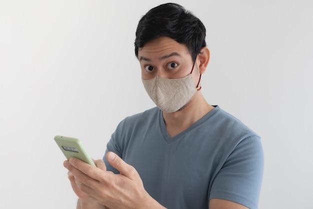 Mężczyzna z maską jest zadowolony ze smartfona
