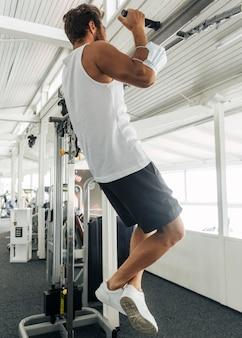 Mężczyzna z maską medyczną na przedramieniu, ćwicząc na siłowni