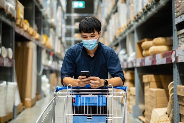 Mężczyzna z maską medyczną patrząc na swój telefon komórkowy i robiąc zakupy w magazynie podczas pandemii koronawirusa
