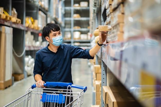Mężczyzna z maską medyczną szuka i robi zakupy w magazynie podczas pandemii koronawirusa