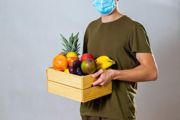 Mężczyzna z maską na twarz, dając klientowi drewniane pudełko z owocami i warzywami.