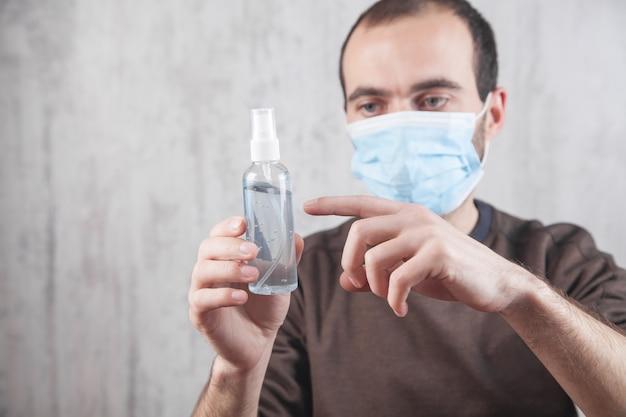 Mężczyzna z maską na twarz pokazujący higienę koronawirusa w żelu odkażającym