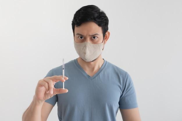 Mężczyzna z maską na twarz wstrzykuje szczepionkę chroniącą przed wirusami