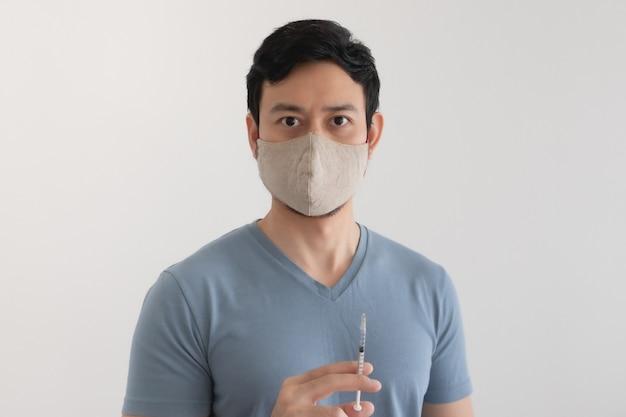 Mężczyzna z maską na twarz wstrzykuje szczepionkę