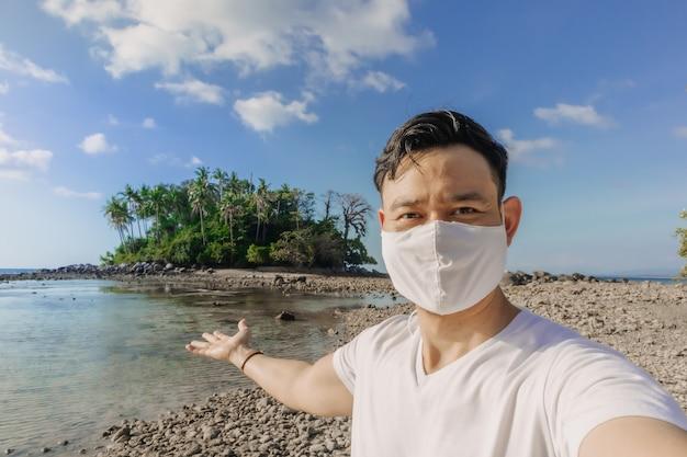 Mężczyzna z maską na twarzy odbywa letnią wycieczkę morską podczas pandemii chowu