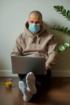 Mężczyzna z maską na twarzy, pracujący na swoim laptopie