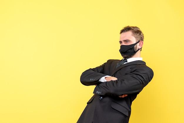 Mężczyzna z maską na twarzy skupiający się i myślący o jednej ważnej kwestii nad żółtym kolorem
