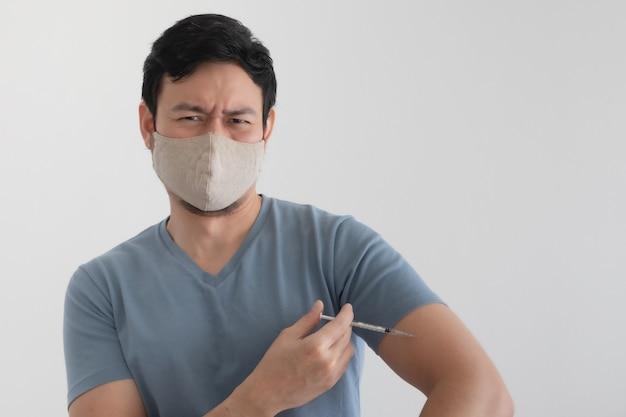 Mężczyzna z maską na twarzy wstrzykuje szczepionkę. pojęcie ochrony przed wirusami.