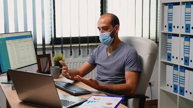 Mężczyzna z maską ochronną za pomocą laptopa do spotkania wideo. freelancer pracujący w nowym, normalnym biurze, rozmawiający na czacie podczas wirtualnej konferencji online, z wykorzystaniem technologii internetowej