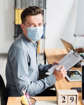 Mężczyzna z maską pracuje w biurze podczas pandemii